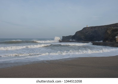 Early Morning Haze on the Beach at Portreath with Atlantic Ocean Waves Crashing into the Harbour Wall part of the South West Coast Path in Rural Cornwall, England, UK
