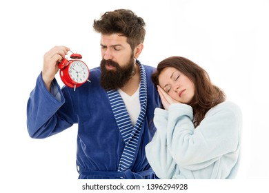 An early morning hour. Sleepy woman and bearded man holding alarm clock early in the morning. Sexy girl and brutal hipster having problem to wake up early. Couple in love being up early.
