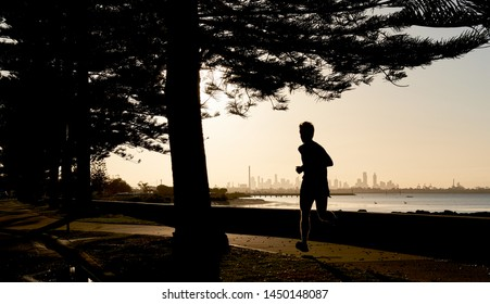 Early morning jogger silhouetted against the skyline of the distance city of Melbourne, Australia.
