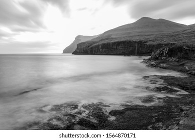 An early morning landscape sunrise view of the coastline of the Faroe Islands at Eidi. The smooth waves along the shoreline lead the eye passed a waterfall and towards the mountains in the background.