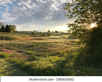 Early morning landscape view of a golf course in the rolling hills of Chester County, PA.  Farm in the distance
