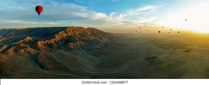 The early morning light illuminates the Theban mountains on the east bank of the Nile near Luxor, Egypt as a flotilla of hot air balloons pass overhead