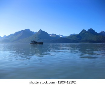 Early morning light illumines the waters of Valdez, Alaska.  A lone fishing vessel sits quietly in front of the Chugach Mountains.