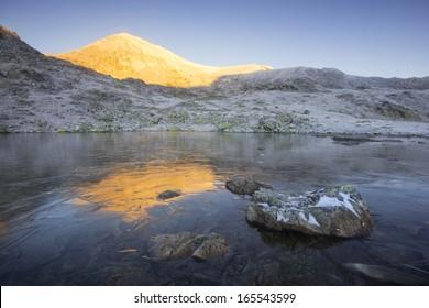 Early morning light on Bucura Peak, reflected in a frosty lake in Retezat National Park, Southern Carpathians, Romania.