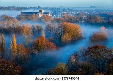 Early morning mist in February on St Catherine's hill on the Hampshire south downs south east England, with Winchester Cathedral rising above to catch the dawn sunlight.