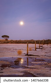 Early morning moonset reflceted in a salt lake with a rustic timber fence and tumbleweed stretching into distance.