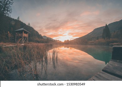 Early morning in the nature reservate of Zelenci, Slovenia, the spring of Sava Dolinka river. Beautiful dreamy morning setting, fairy tale vivid colors and still lake visible.