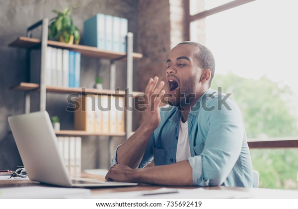 Early morning in the office. Sleepy tired freelancer is yawning at his work place in front of the laptop`s screen on desk top