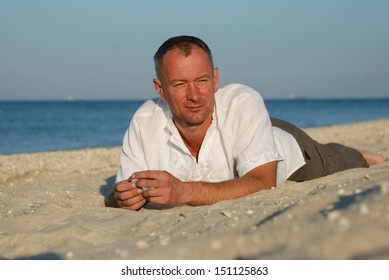 Early morning on the Azov Sea. Man resting on the beach