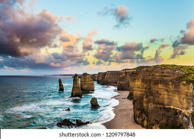"""Early morning on the ocean shore. Pink dawn clouds over the famous rocks """"Twelve Apostles"""". Travel to Australia. The concept of active, ecological and photo tourism"""