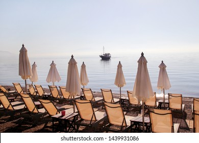 Early morning on sandy beach without people with empty chaise lounges, sun beds, sunshades, summer umbrella parasol, deck chairs, table, loungers for sunbathing on ocean beach waiting for tourists.