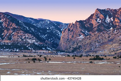 Early morning pink alpenglow touches Eldorado canyon in the foothills of the Colorado Rocky Mountains near Boulder