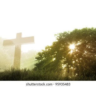 Early morning rays of sunlight and religious cross. Copy space