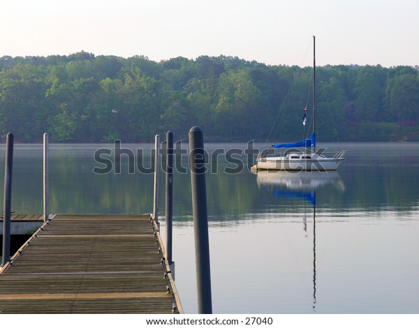 Early morning serene scene lakeside with a lone sailboat moored in the lake.