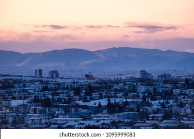 Early morning shot of modern urban development in Reykjavik, Iceland in front of snow covered mountains and fjords in winter.