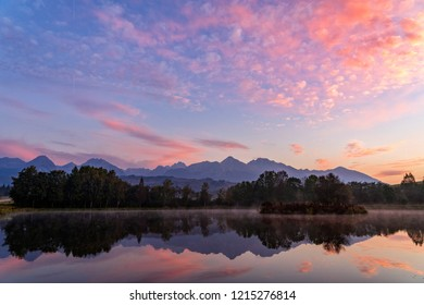 Early morning shot of peaceful scene of beautiful autumn mountain landscape with lake, colorful trees and high peaks and red sky in High Tatras, Slovakia.