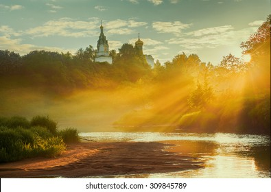 Early morning in small russian village with orthodox church at the hilltop