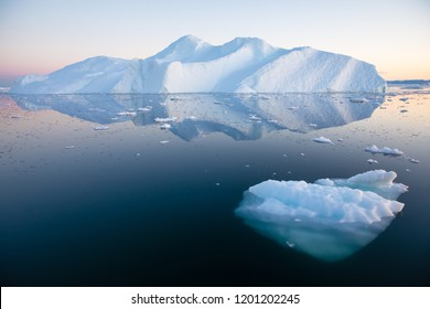 Early morning summer alpenglow lighting up icebergs during midnight season. Ilulissat, Greenland.