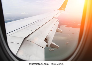 Early morning with sun light shedding onto wing airplane cover by airplane window frame, It's look like airplane preparing for landing, concept travel and freedom.