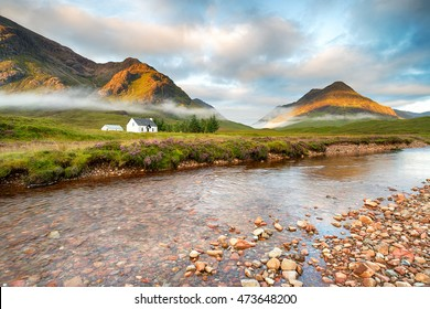 Early morning sun lights the mountain tops at Glencoe in the Scottish Highlands