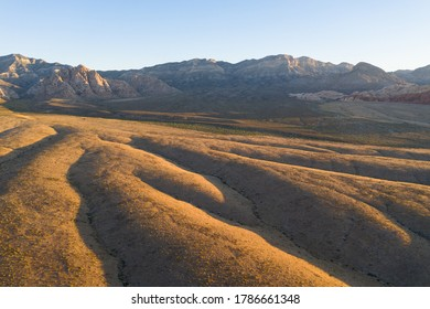 Early morning sunlight illuminates a beautiful mountain landscape that rises from the desert surrounding Las Vegas, Nevada. This desert area averages over 95 degrees F during summer months.