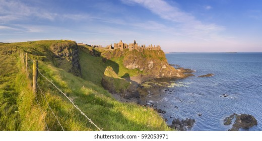Early morning sunlight over Dunluce Castle at the Causeway Coast of Northern Ireland.
