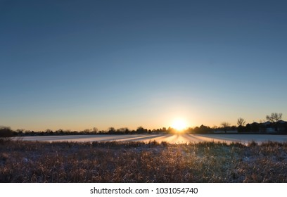 Early morning sunrise across frozen lake at local park with clear blue skies on a cold Winter day. Photo shot locally December 2017.