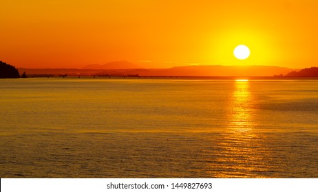 Early morning sunrise behind the mountains with sunlight reflection on the ocean/river. Landscape silhouette at dawn as the sun brings light to the sea coast. Start of the day with beautiful sunshine.