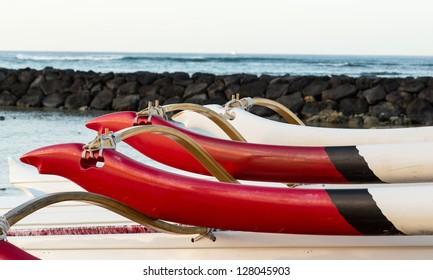 Early morning sunrise at dawn illuminates outrigger of traditional Hawaiian canoe in Waikiki Beach area of Oahu in Hawaii