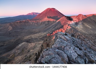 Early morning sunrise, landscape scenery of blue lake, wild mountains and huge volcano, autumn colours and golden sun rays, Tongariro National Park New Zealand North Island