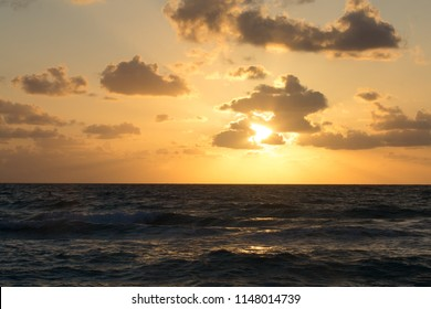 An early morning sunrise over Biscayne Bay viewed from Miami beach. Scattered clouds are back lit by an orange and yellow sun as it begins to ascend above the horizon.
