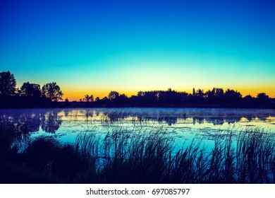 Early morning, sunrise over lake. Misty morning, rural landscape, wilderness, mystical feeling