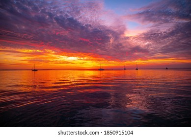 Early morning, sunrise over sea. Ocean sunset on sea water with a colorful vivid sunset sky and silhouettes of sailboat in the background - Shutterstock ID 1850915104
