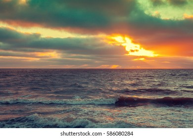 Early morning, sunrise over sea with dramatic cloudy sky. Stormy weather. Waves on the sea. Twilight time.