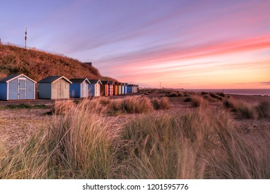 Early morning sunrise photo of a group of beach huts on Pakefield Beach in Lowestoft, Suffolk in England.