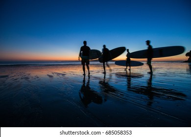 Early morning surfers at sunrise on Takapuna Beach, New Zealand overlooking Rangitoto island. getting ready to paddle longboards together as a group and as a team