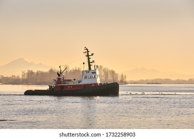 Early Morning Tugboat. A tugboat departs the calm water of Steveston Harbor in British Columbia, Canada near Vancouver.