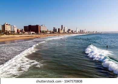 """Early morning view of beach waves and ocean shoreline against Durban """"Golden Mile"""" beachfront city skyline and blue sky in South Africa"""