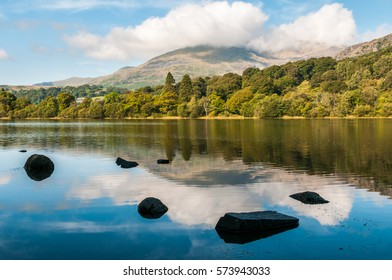 An early morning view of Coniston Water in the English Lake District. The summit of Coniston Old Man in the background is hiding in the clouds.
