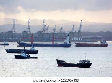 The early morning view of different size cargo ships with Colon town port in a background (Panama).