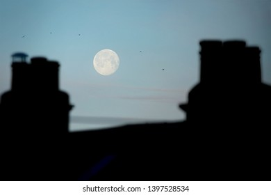 Early morning view of the full moon over the rooftops of Bath, England, UK