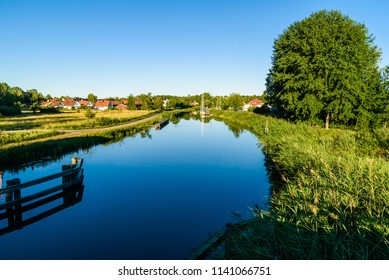 Early morning view of the Gota canal with boats moored at a marina in the distance. Location Norsholm, Sweden.
