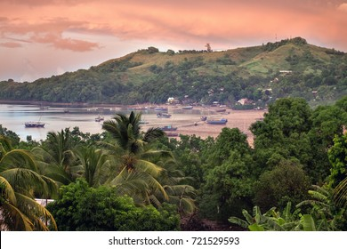 Early morning view over a bay near Hell Ville on Nosy Be, Northern Madagdascar after a tropical storm; ships lie on the beach at low tide.