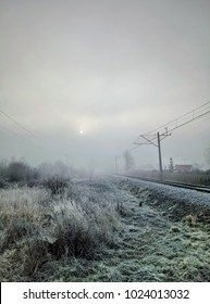 Early morning view of rails and sun above the smog and fog. Cold weather, frozen grass, pea soup, killer fog. Railway apocaliptyc scenery. Ice and frost. Urban and rural. Industrial, apocalypse scape.