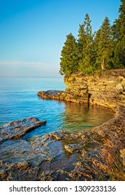 Early morning view of a rocky cliff on the coast of Lake Michigan in Door County Wisconsin.