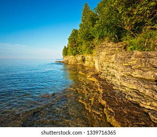 Early morning view of a rocky coastline cliff on the coast of Lake Michigan from Cave Point Park in Door County Wisconsin.
