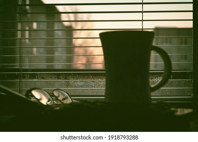 Early morning in winter, awakening, view from the window through the blinds. Black silhouette of a mug, an open book and glasses on the windowsill. Light and shade. Loneliness and melancholy.