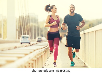 Früh morgens Training. Fröhliches Paar, das über die Brücke lief. Gesunder Lebensstil.