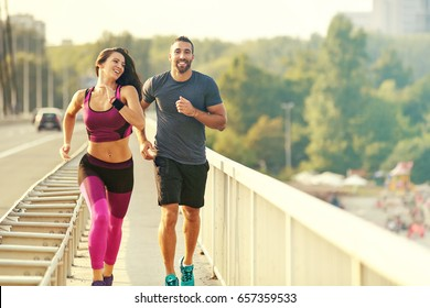 Early morning workout. Happy couple exercising on the bridge. Living healthy lifestyle.