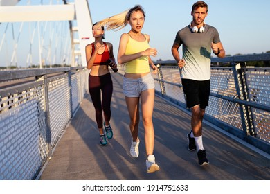 Early morning workout. Happy people running across the bridge. Living healthy lifestyle.
